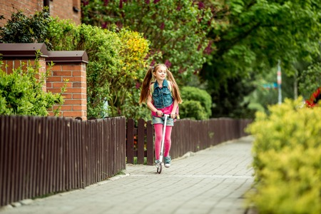 Little girl with a backpack goes to school on a scooter