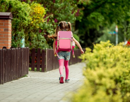 kleines Mädchen mit einem Rucksack in die Schule gehen. Rückansicht