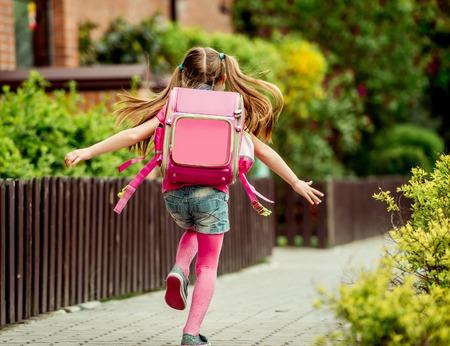 ni�o escuela: ni�a con una mochila correr a la escuela. vista trasera