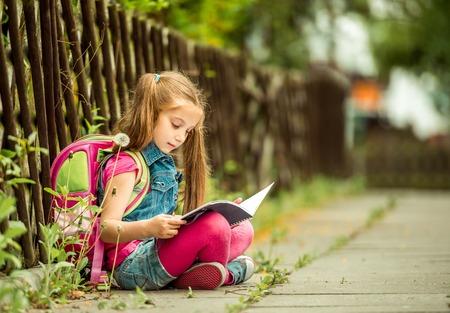 colegiala: La pequeña colegiala leyendo un libro sentado en la calle