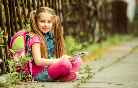 sitting pretty: Little pretty schoolgirl reading a book sitting on the street