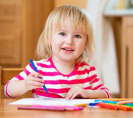 niños pintando: Linda niña de tres años de edad se basa rotuladores en casa Foto de archivo