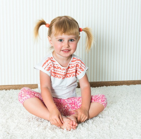 attivit�?  fisica: 2-year-old girl engaged in physical activity at home