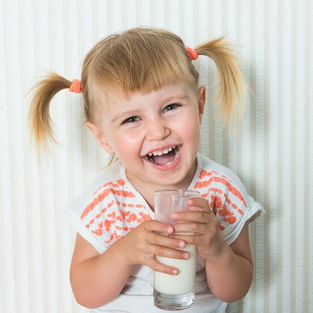 vaso de leche: 2-años de edad, niña bebe la leche en el suelo en su casa. de cerca
