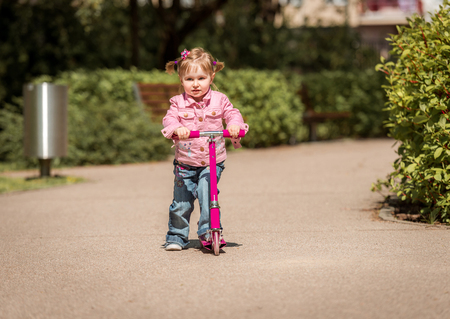 girl sport: Two years old girl riding her scooter on the park