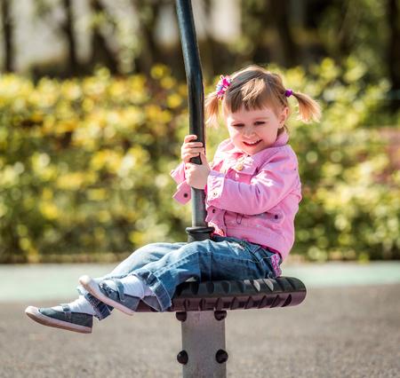 playground equipment: Cute little girl on outdoor playground equipment