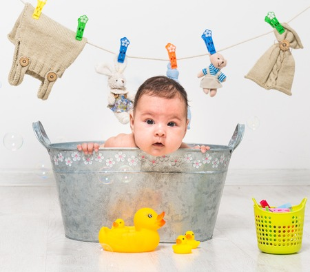 wash basin: little two-month girl bathes in a  trough and dry her clothes Stock Photo