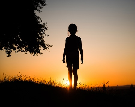 teen girls: silhouette of a beautiful teen girl standing on a background of gorgeous sunsets Stock Photo