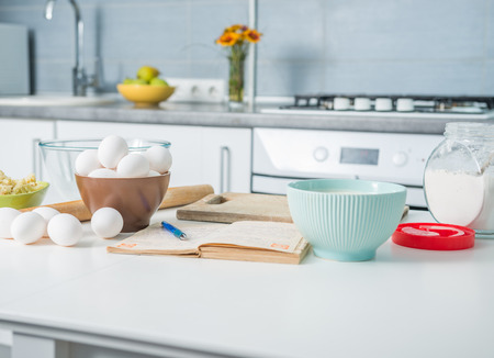 ingredients for baking and recioe book on a kitchen table Standard-Bild