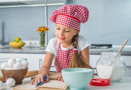 recipe book: little girl baker reading a recipe on kitchen