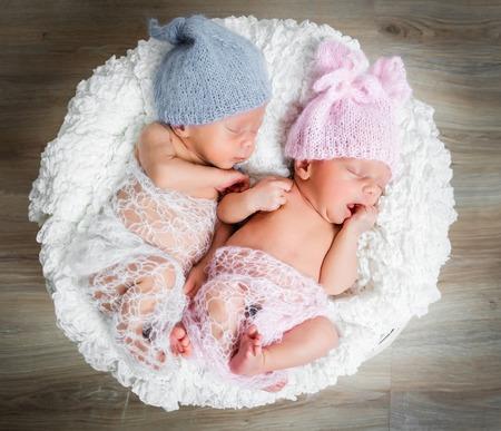 Gemelos recién nacidos - un niño y una niña durmiendo en una cesta Foto de archivo - 43785640
