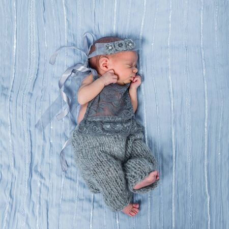 jumpsuit: sleeping newborn baby girl in a gray jumpsuit with decoration on her head Stock Photo