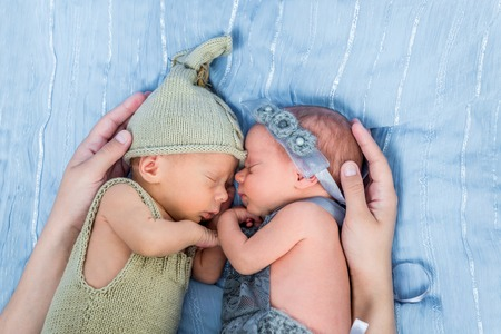 blue blanket: mothers arms wrapped around newborn twins  sleeping on a blue blanket