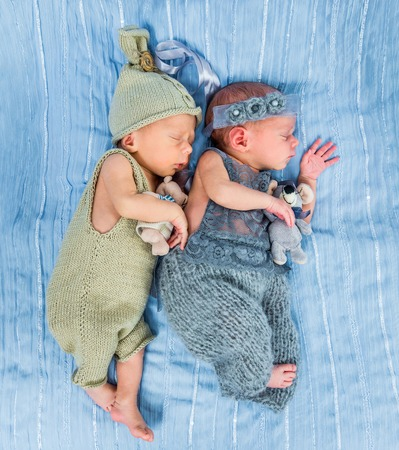 blue blanket: newborn twins  sleeping with toys on a blue blanket Stock Photo
