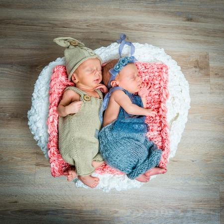 gemelos recién nacidos - un niño y una niña durmiendo en una cesta