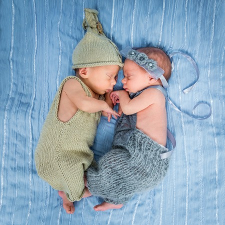 blanket: newborn twins - a boy and a girl sleeping on a blue blanket Stock Photo