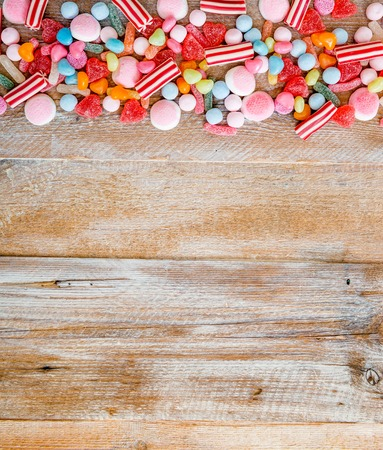 candy: variety of candies on a wooden background with space for text