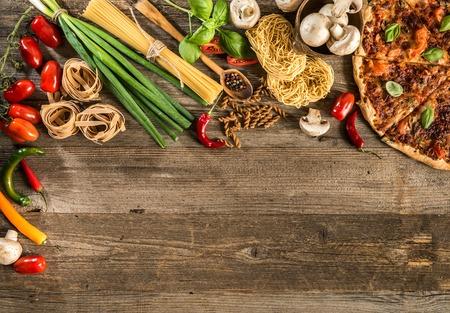 Italienisches Essen Hintergrund mit Pizza, Roh Nudeln und Gemüse auf Holztisch