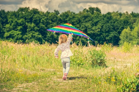 little cute girl flying a kite in a meadow on a sunny day, back view Stock Photo