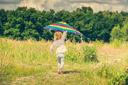 dia soleado: niña linda que vuela una cometa en un prado en un día soleado, la vista atrás Foto de archivo