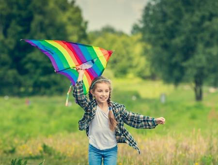 papalote: niña linda que vuela una cometa en un prado en un día soleado Foto de archivo