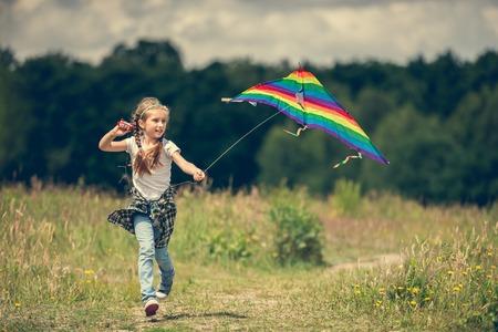 arco iris: niña linda que vuela una cometa del arco iris en una pradera en un día soleado