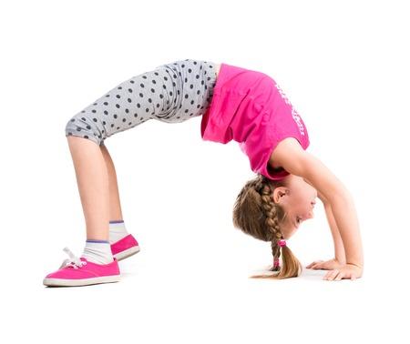 little girl doing the bridge exercise isolated on white background Foto de archivo