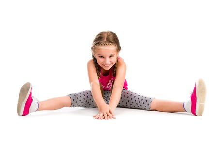 little girl doing yoga isolated on white background Foto de archivo