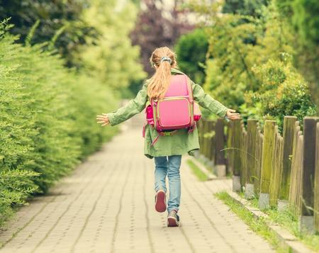 Dziewczynka z plecakiem idzie do szkoły. widok z tyłu