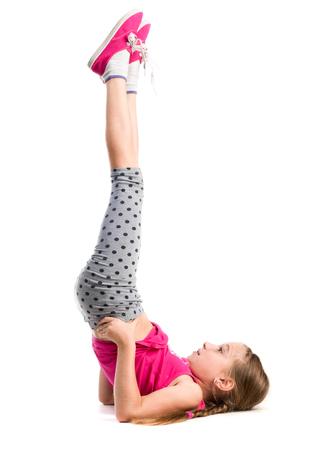 klein meisje met benen op oefening geïsoleerd op een witte achtergrond