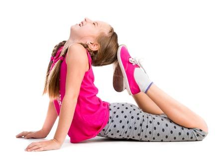 pies bonitos: niña haciendo un ejercicio en el suelo aislado en el fondo blanco Foto de archivo