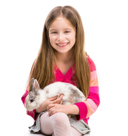 baby girl: cute smiling girl in a crimson sweater  with baby rabbit over white background close-up Stock Photo