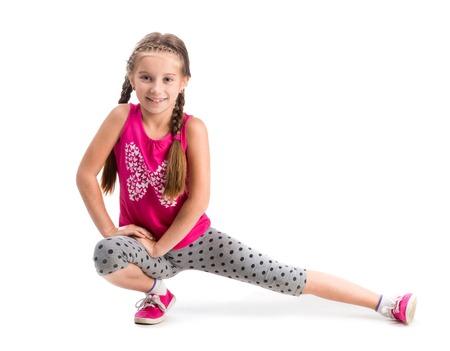 doing: smiling little girl doing exercise isolated on white background