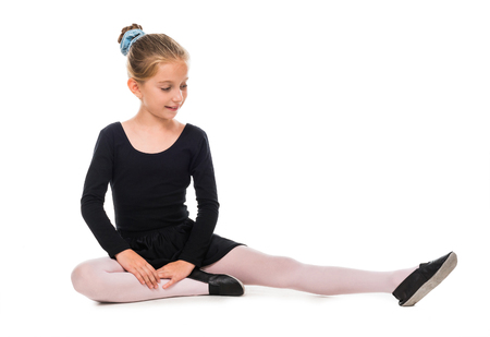 ballerina shoes: smiling little stretching on the floor isolated on white background Stock Photo