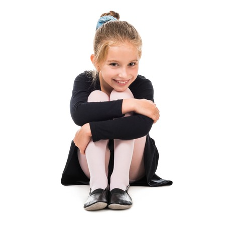 skirts: smiling little gymnast on the floor isolated on white background