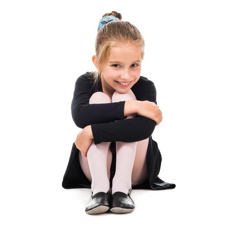 skirts: sonriente poco gimnasta en el suelo aislado en el fondo blanco Foto de archivo