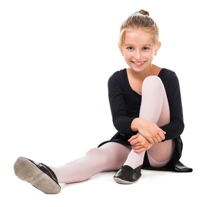turnanzug: lächelnden kleinen Turnerin auf dem Boden isoliert auf weißem Hintergrund