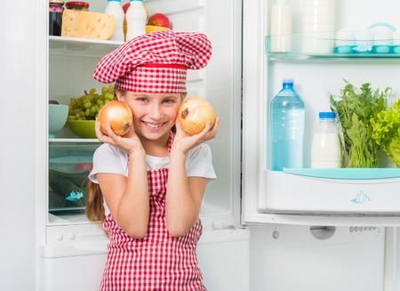 onion: ni�a cocinar sosteniendo cebollas grandes cerca de las mejillas cerca de nevera abierta Foto de archivo