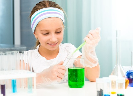 science experiments: cute little girl with flasks for chemistry