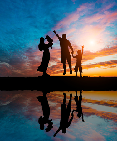 Silhouettes of happy parents having good time with their little children on the seacoast 免版税图像