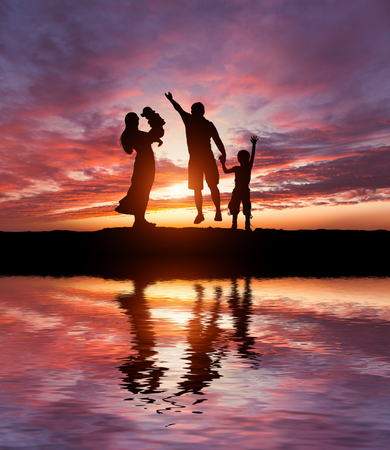 person walking: Silhouettes of happy parents having good time with their little children on the seacoast Foto de archivo