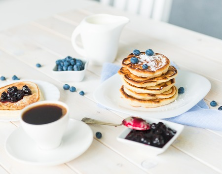 blueberry jam: pancakes with blueberry and jam on white wooden table Stock Photo