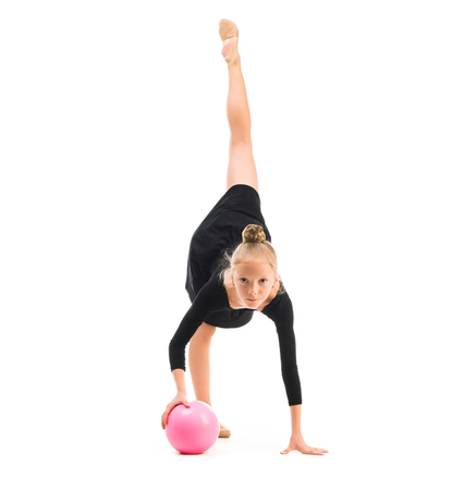 children sport: little gymnast doing exercise with ball isolated on white background