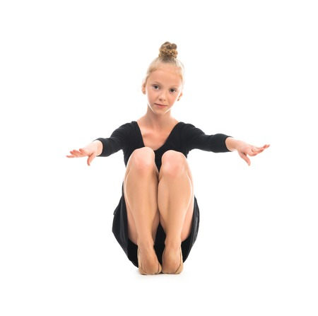 girl sport: little gymnast stretching on the floor isolated on white background