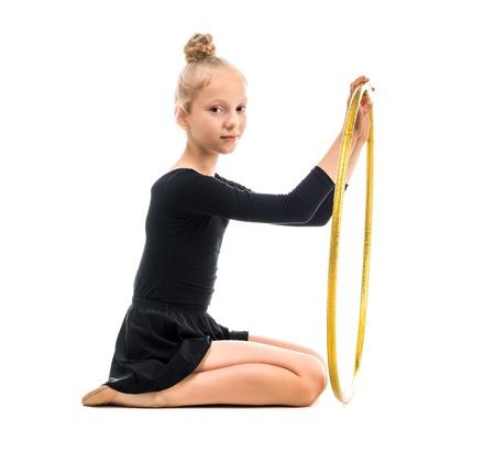 白い背景で隔離のフープで運動をやっている小さな体操選手 写真素材