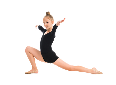 rhythmic gymnastics: little gymnast stretching on the floor isolated on white background