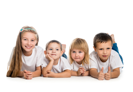 standing together: smiling children lying on the floor isolated on white background