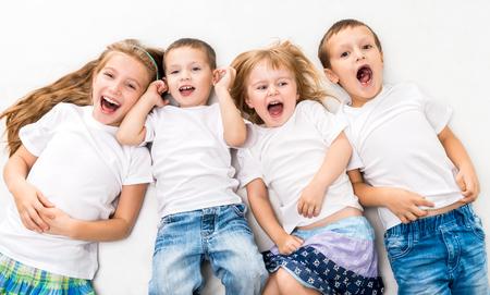 白い背景で隔離床に横になっている白いシャツの子供たち 写真素材