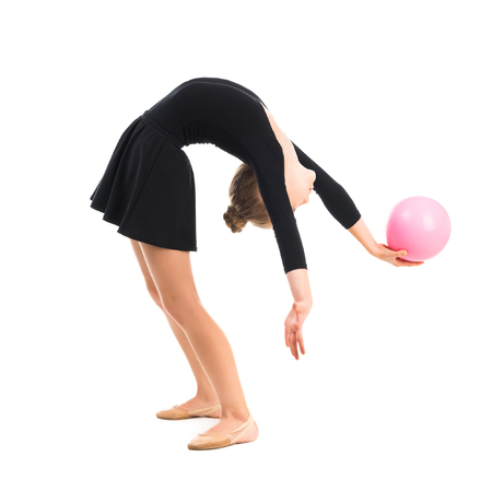 gimnasia: peque�a gimnasta haciendo ejercicio con bola aislado en el fondo blanco Foto de archivo