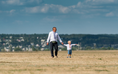 airshow: UKRAINE, KHARKIV -AUGUST 24: father and son on a fiel for airshow on Ukraine Independence Day at Kharkiv  on August 24, 2015 Editorial